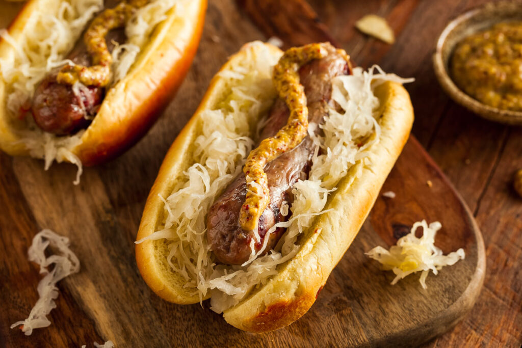 air fryer brats on a wooden board topped with mustard and sauerkraut
