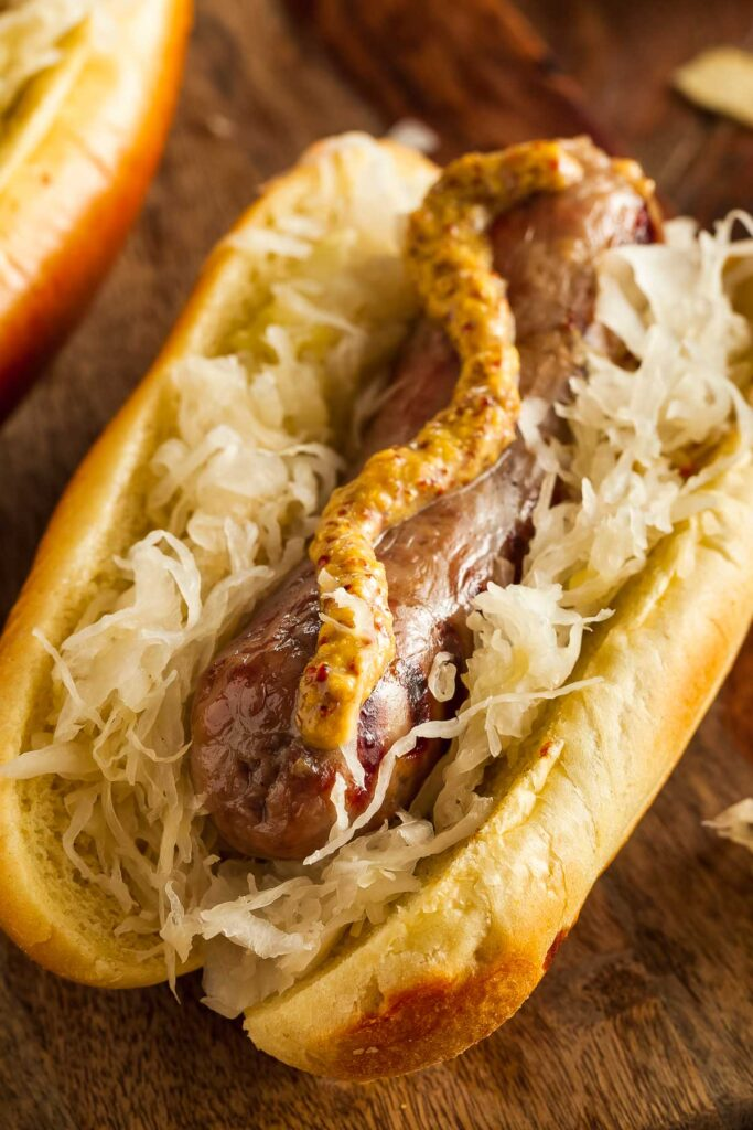 a closeup of air fryer brats on a wooden board topped with mustard and sauerkraut