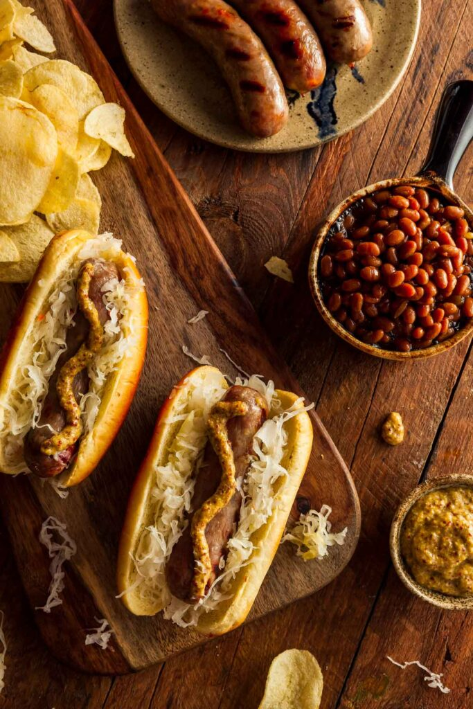 air fryer brats on a bun topped with mustard and sauerkraut next to a bowl of baked beans