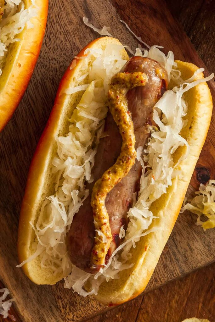 brats made in the air fryer on a bun topped with mustard and sauerkraut