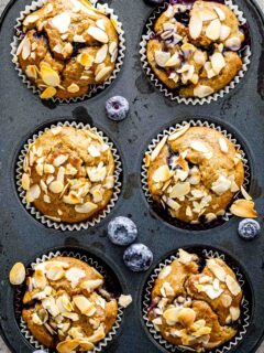 a closeup of banana blueberry oatmeal muffins in a muffin pan just out of the oven