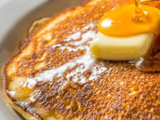 a closeup of short stack of carbquik pancakes on a white plate topped with butter and maple syrup