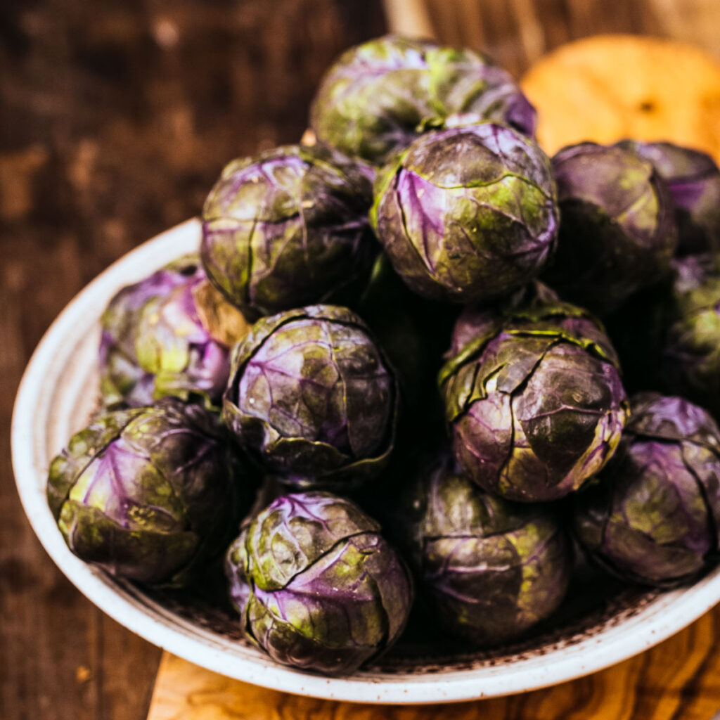 a bowl of raw purple brussels sprouts