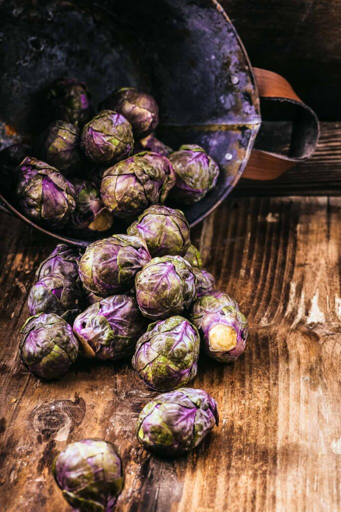 purple brussels sprouts spilling out onto a wood cutting board