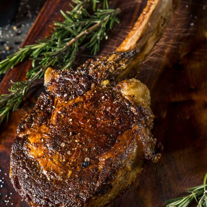 a tomahawk steak out of the oven on a cutting board next to fresh rosemary