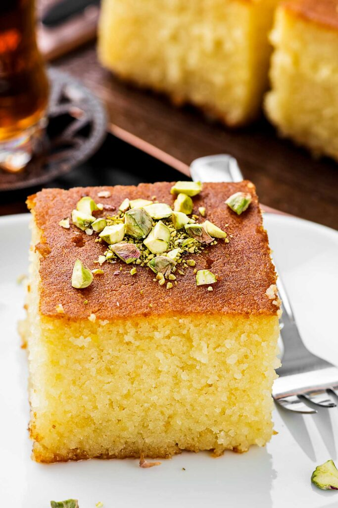 a closeup of a slice of revani turkish cake on a white plate garnished with pistachios