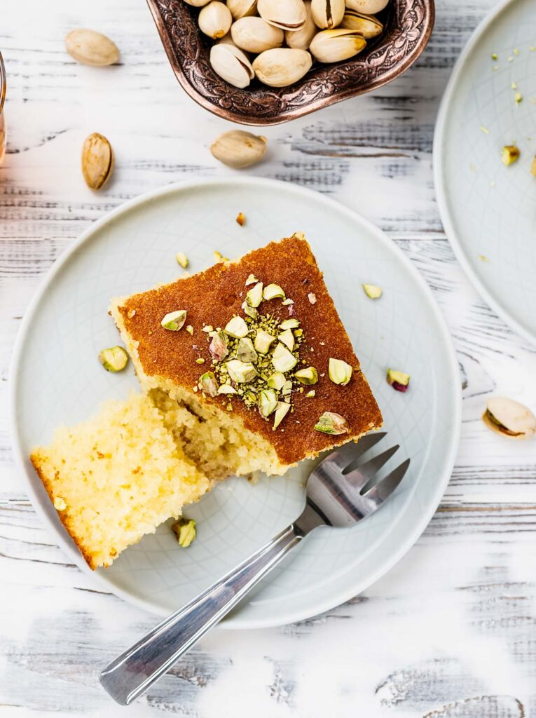 an overhead shot of a slice of revani turkish cake on a white plate garnished with pistachios
