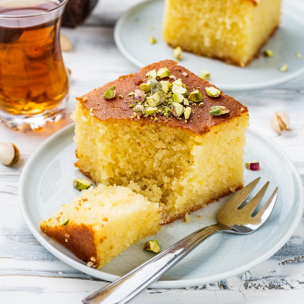 a slice of revani turkish cake on a white plate garnished with pistachios