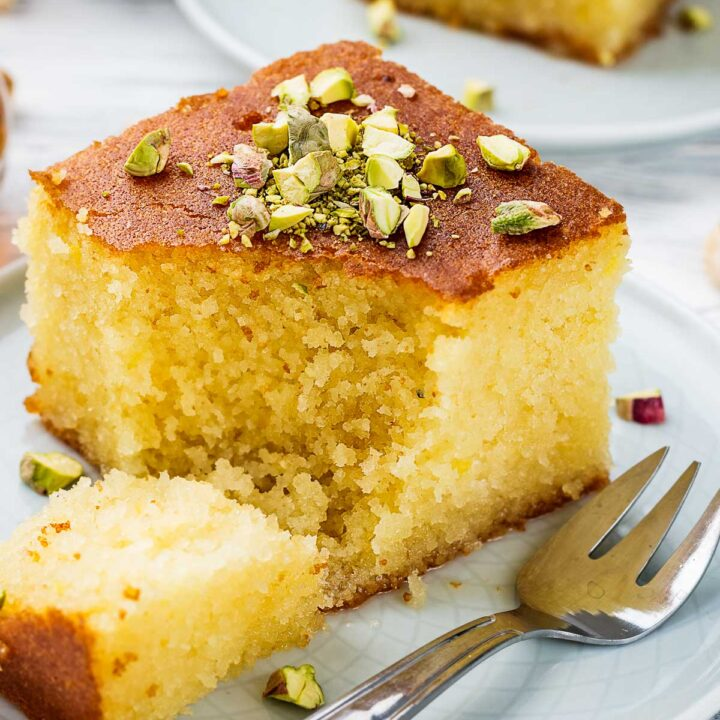 a closeup of a slice of revali turkish cake on a white plate garnished with pistachios